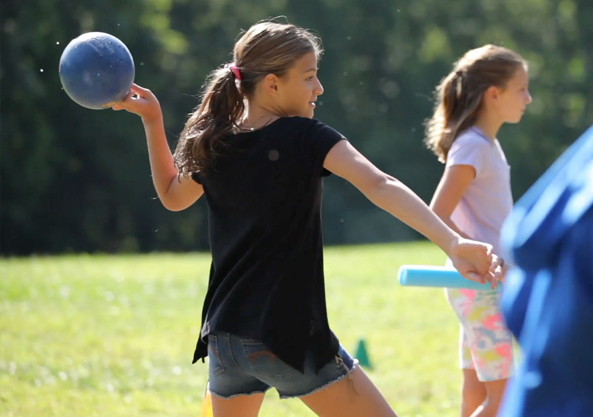 Girl in black shirt getting ready to throw a blue ball outside