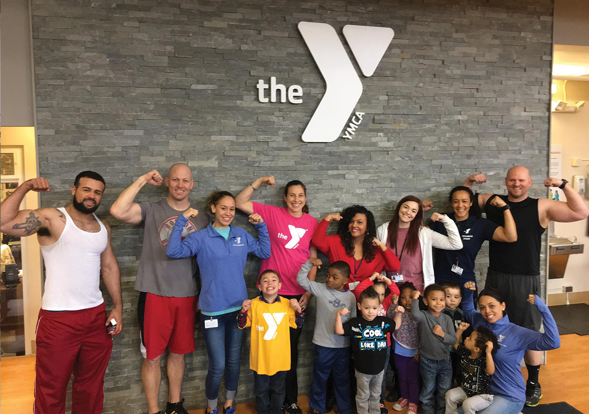 Group of YMCA staff and young kids standing in front of Waterbury YMCA main office sign