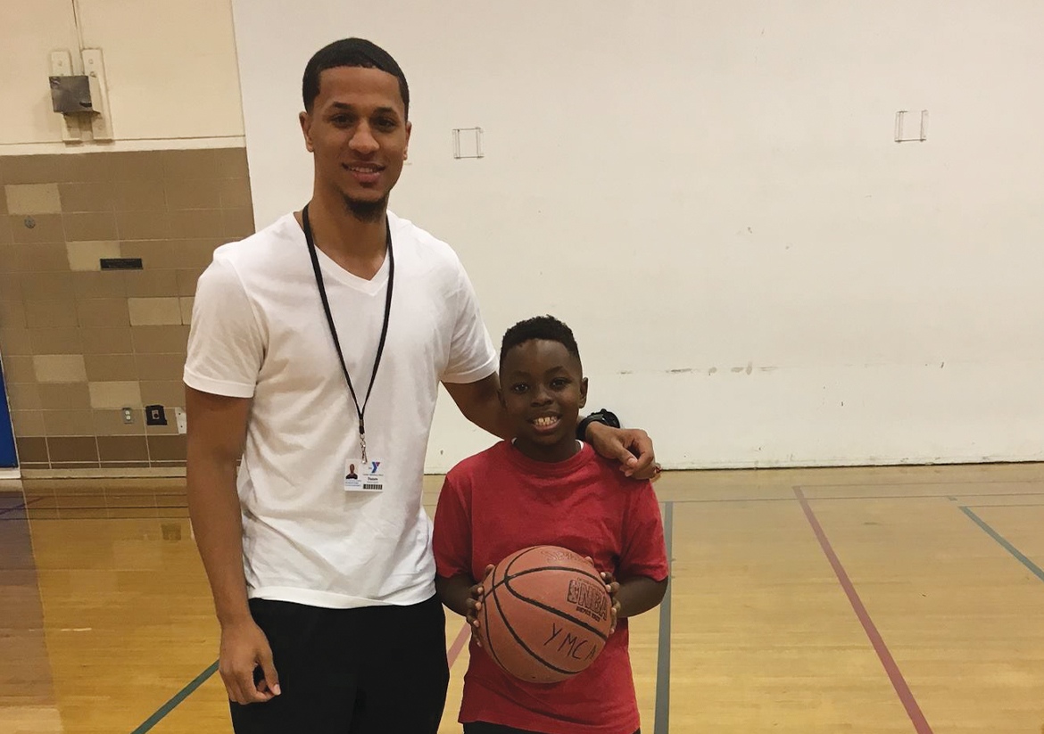 Male YMCA staff smiling for a picture with a young boy holding a basketball