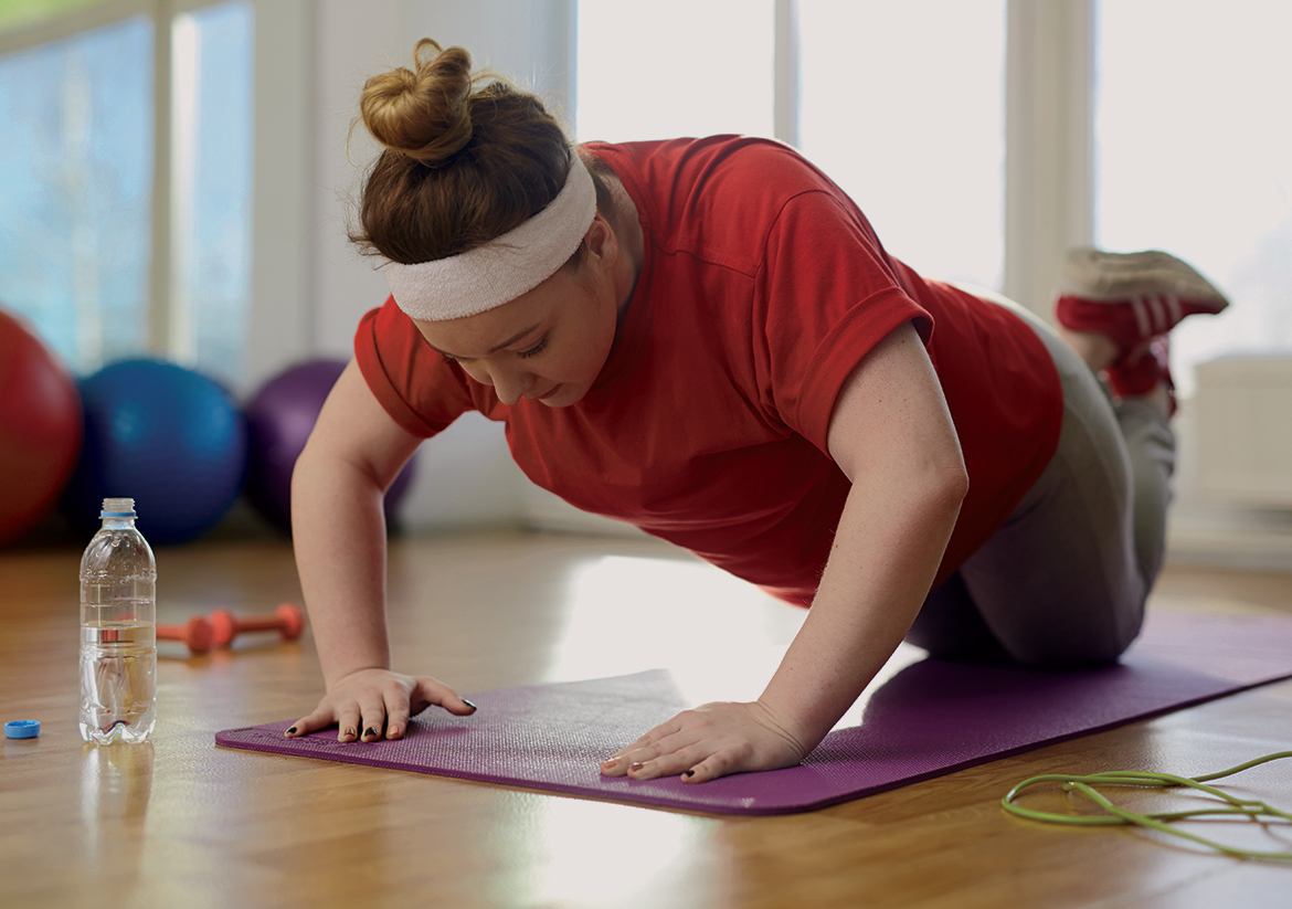 Young woman in red shirt and white sweatband doing a push-up on a purple yoga mat