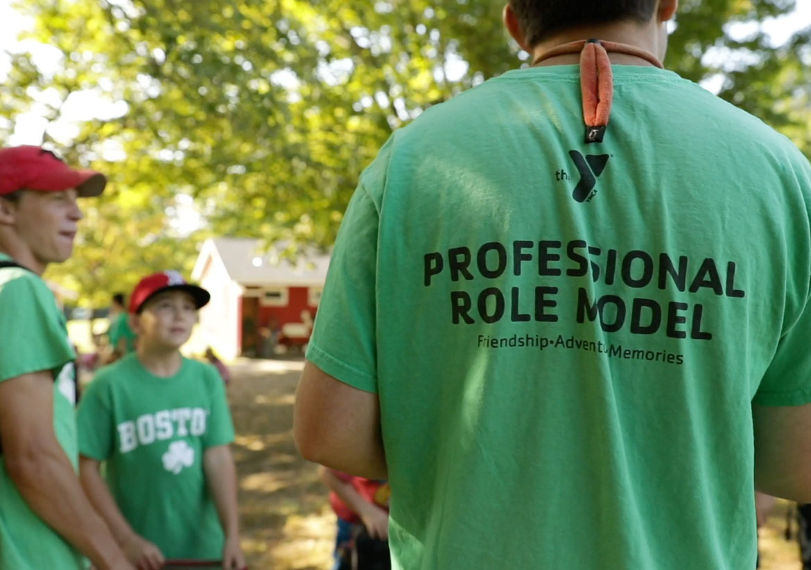 The back of a green YMCA staff shirt that says Professional Role Model
