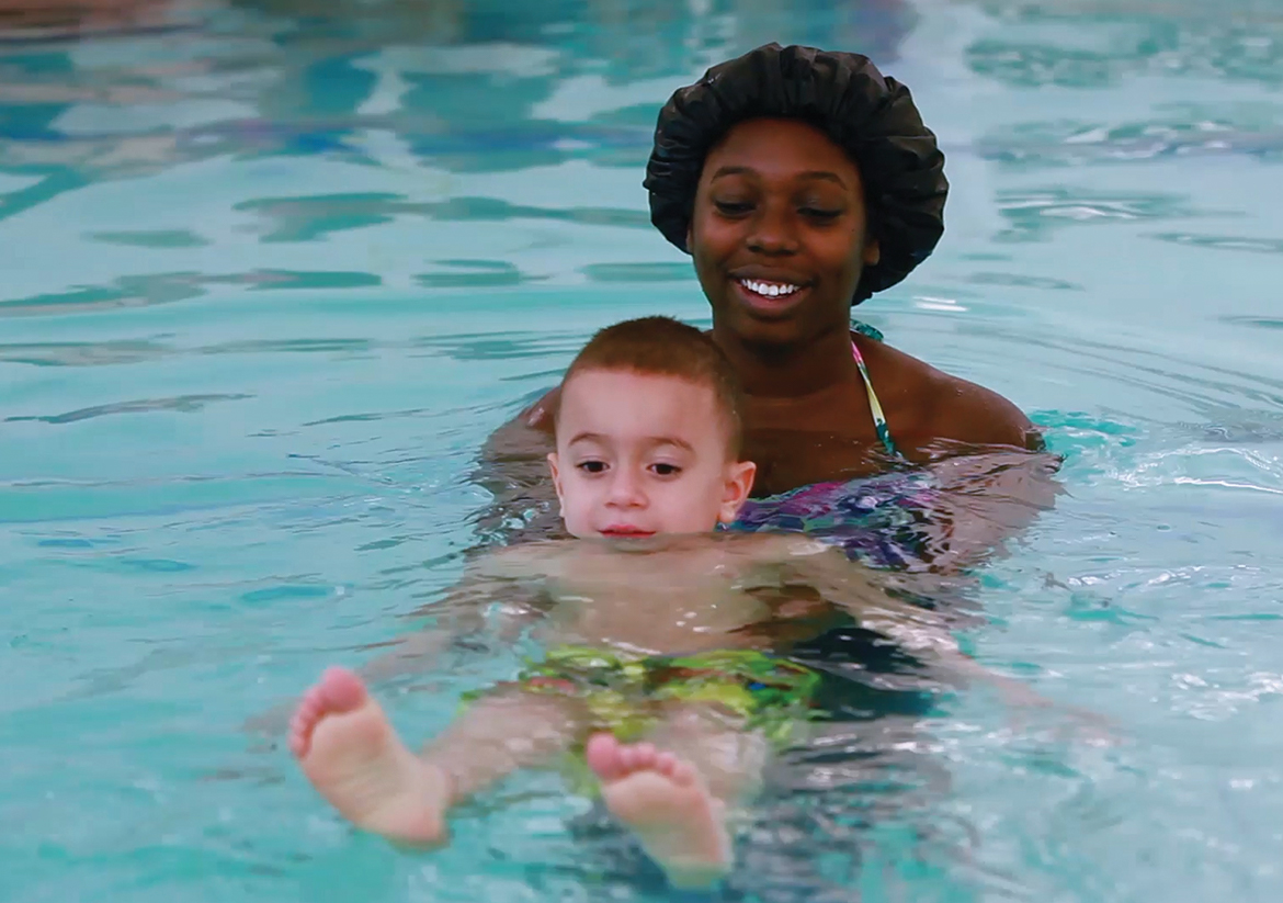 Female swim instructor teaching a little boy to swim in the pool