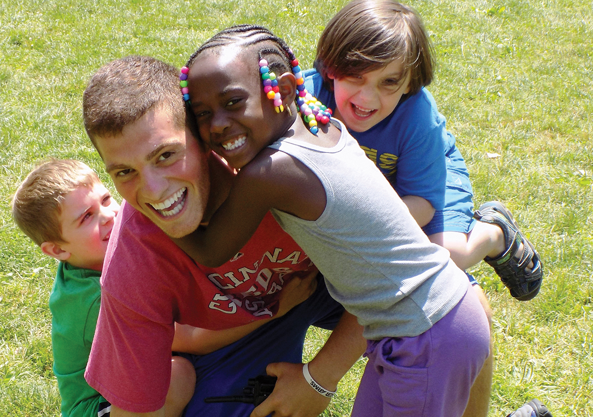 Three young kids smiling and hugging their YMCA camp counselor