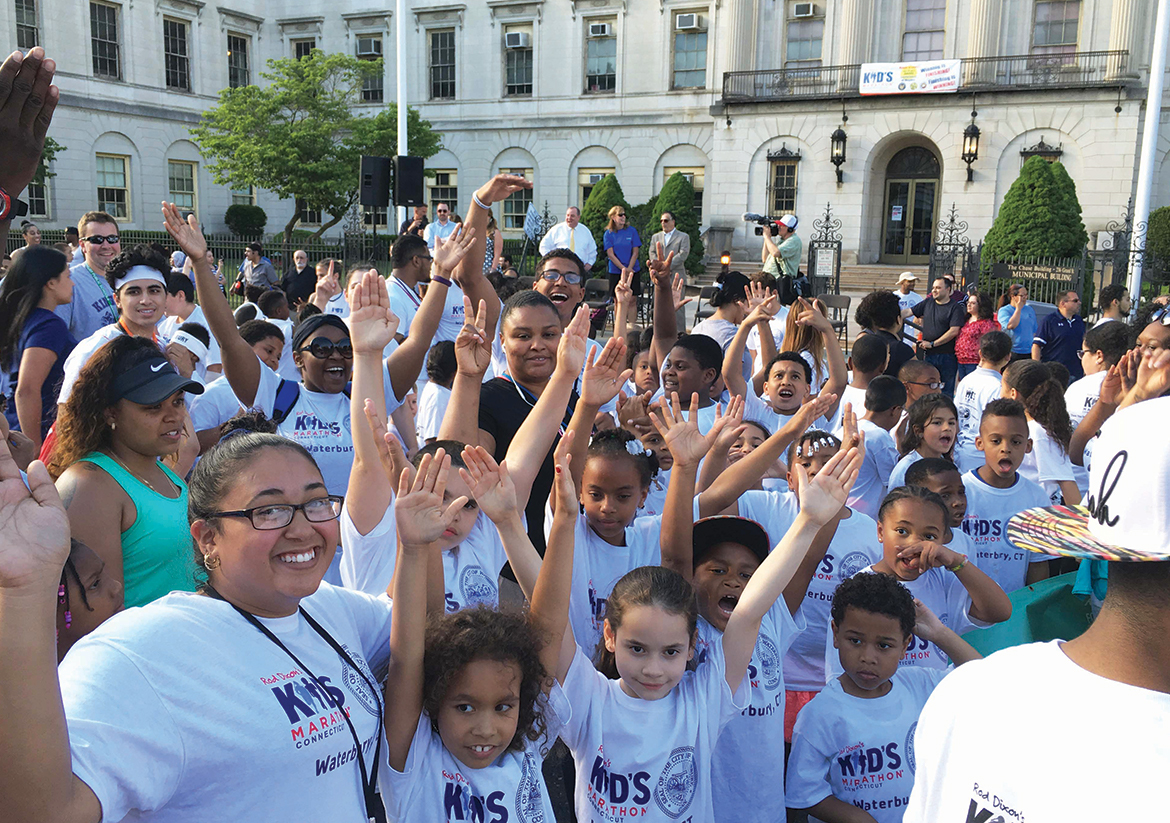 Group of kids and adults smile and raise their hands at a YMCA event