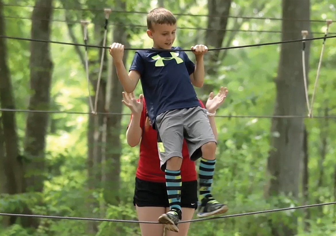 Young boy on the ropes course at Camp Mataucha