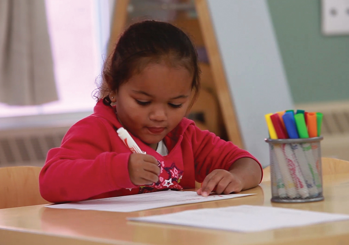 Little girl in pink sweatshirt sitting at a desk coloring with markers