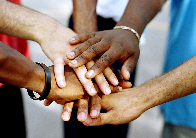 Group of several hands coming together one on top of each other