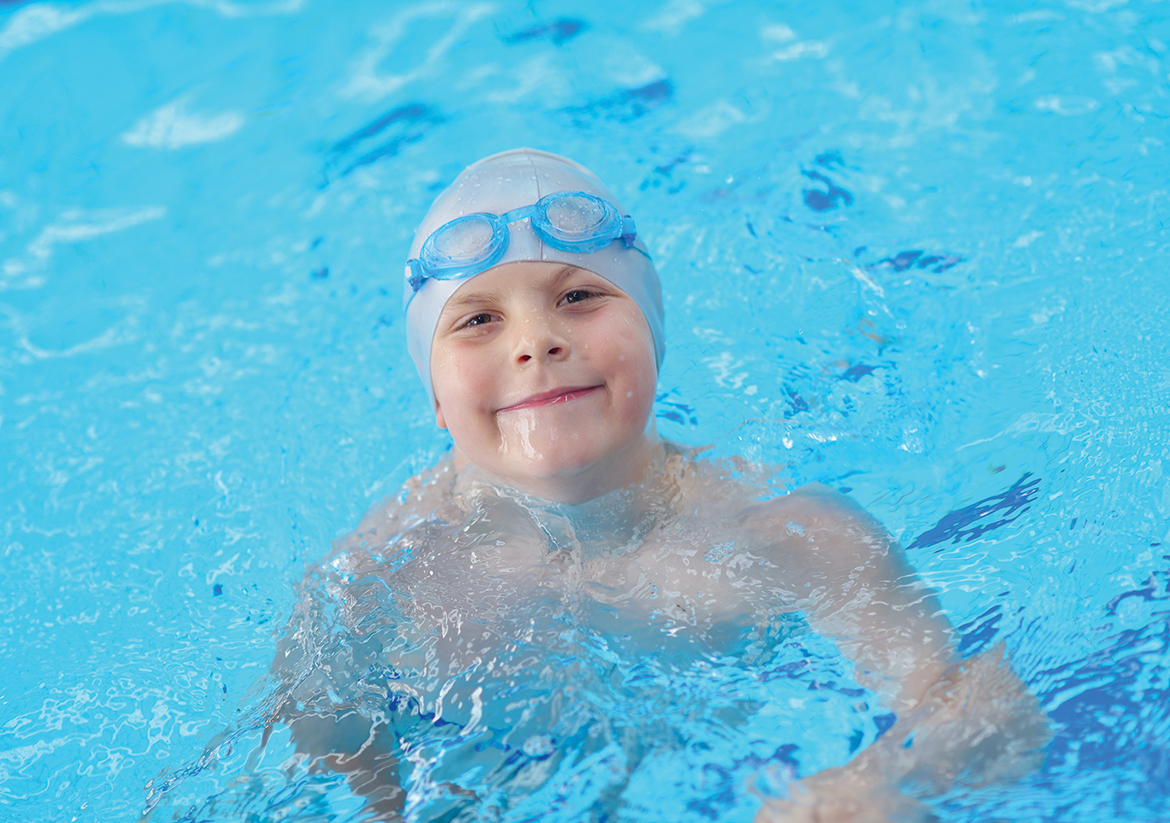 Young child in swim cap smiling at the camera in a pool